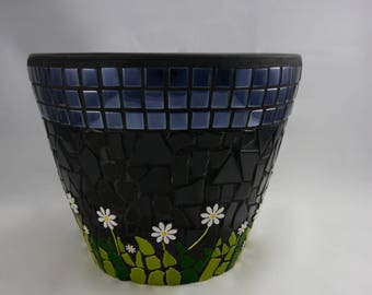 Large plant pot with daisies in the grass during night time.