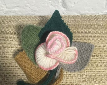 crocheted flower blooming pin