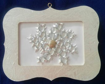 Snowflake made with glass disks and pearl white paint on wooden frame.