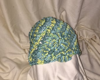 Light green, blue, and yellow beanie with flowery decal