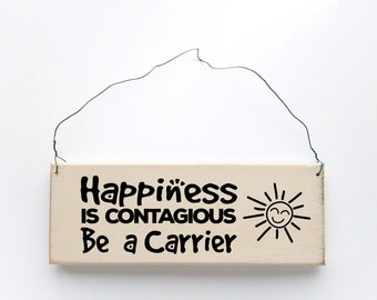 """Wood sign saying """"Happiness is Contagious Be A Carrier"""" Antique white wired sign."""