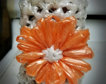 Plastic bag crocheted drink cozy with flower