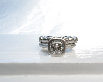 Platinum and cushion cut diamond solitaire low profile bezel set engagement ring with matching diamond eternity ring