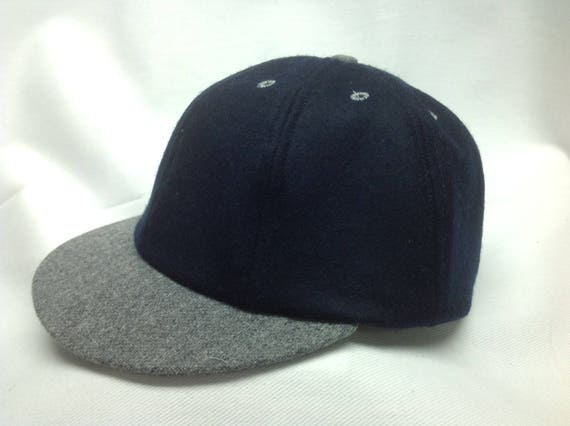 Navy Melton wool cap with dark grey wool flannel visor and button. Custom made to any size.