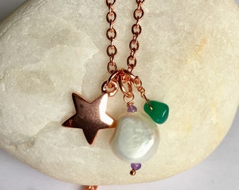 Long rose gold plated star pendant with baroque pearl .