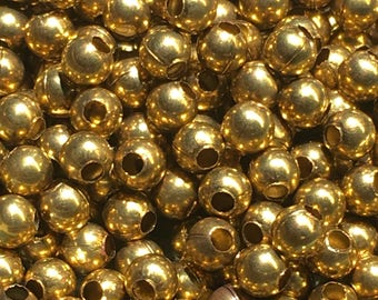 50 tiny brass round beads with center hole vintage old