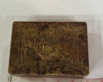 Vintage Hand Carved Stone Dresser Box. Four sides with Floral Carving. Lid has an Oriental Scene Carved. Lid has a chip. Base has a a chip.