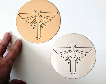The Last of Us sticker / decal, metallic silver and gold. Fireflies symbol from TLOU and TLOU2, laser engraved. Great for laptops!