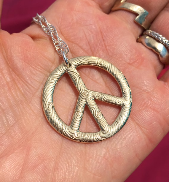 Large Gold Peace Vibe Necklace hung on Sterling Silver Chain