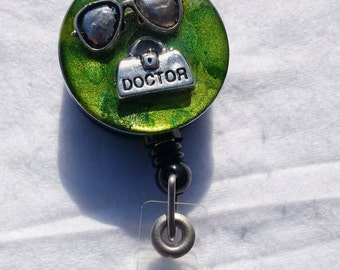 Optometrist name badge holder with sunglass and doctor bag detail on a green background