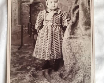 Antique cabinet card of cute little girl in winter clothes