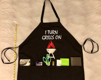 I Turn Grills On - Black Apron with White Text and Silver Grill with Flames