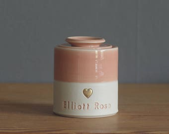 custom infant urn with ceramic lid. gold accent stamp, straight shaped urn with heart stamp. modern simple urn for ashes. peach pink urn.