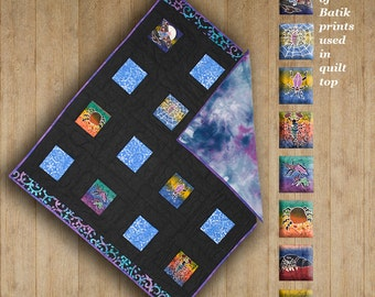 Unique batik childs blanket. Hand-dyed shades of purples & blues cotton flannel back. Top in shades of charcoal and rainbow.
