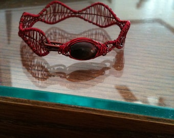 Brilliant cherry red wrapped around a brown copper wire frame and finished with rich dark stained wooden bead