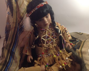 """Native American Indian porcelain doll beaded ethnic faux suede costume & dreamcatcher black braided hair sits 11"""" on fur trimmed mat"""