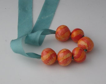 Red and tangerine small striped round bead