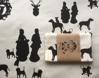 Screen-printed tea towel with silhouettes featuring figurines, dogs and a stag's head