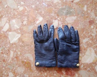 black leather gloves with a golden turtle button