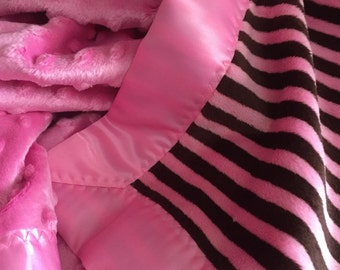 A  bubble gum pink and brown stripe design minky blanket , it has a pink satin binding around it.