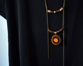 Pendant necklace with metal chain and felt spirals orange brown
