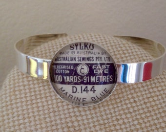 Vintage Spool label bangle / bright silver and glass cabochon / dewhursts sylko marine blue label / sewing theme gift / upcycled cotton reel