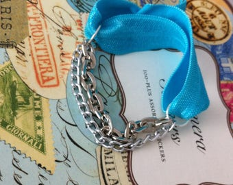 Silver chains and blue elastic bracelet