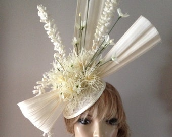 Vintage skull cap design adorned with cream lace detailing ivory and cream flowers finished with a dramatic sculptured gen seng bow.