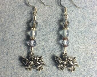 Silver lovebird charm dangle earrings adorned with light blue Czech glass beads.