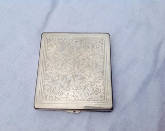 Compact small and engraved white metal