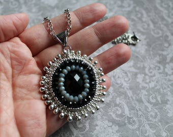 Oval bead embroidery pendant with onyx facetted cabochon