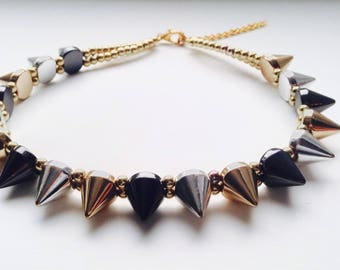 Punk spike choker necklace with an adjustable fastener. Gold / silver / black