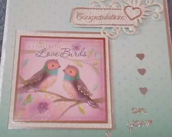 Congratulations on your engagement card. Features two colourful love birds on a pale green background.
