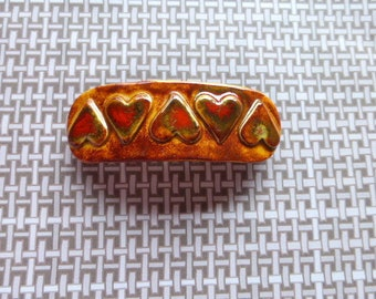 """Ceramic Barrette. 3 1/4"""" long. 1 1/8' wide. Golden brown with red and yellow highlights."""