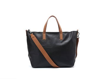 Simple black leather tote bag with contrasting brown handles and shoulder strap