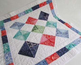 Quilted Square Batik Table Topper welcomes Summer in bright colors of blue, coral and white