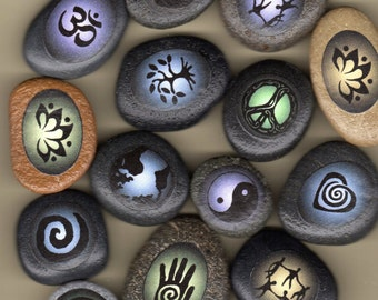 boda stones with symbols; spiral heart, healing hand, peace, yin yang, lotus, tree, community dancers, earth, spiral, ohm