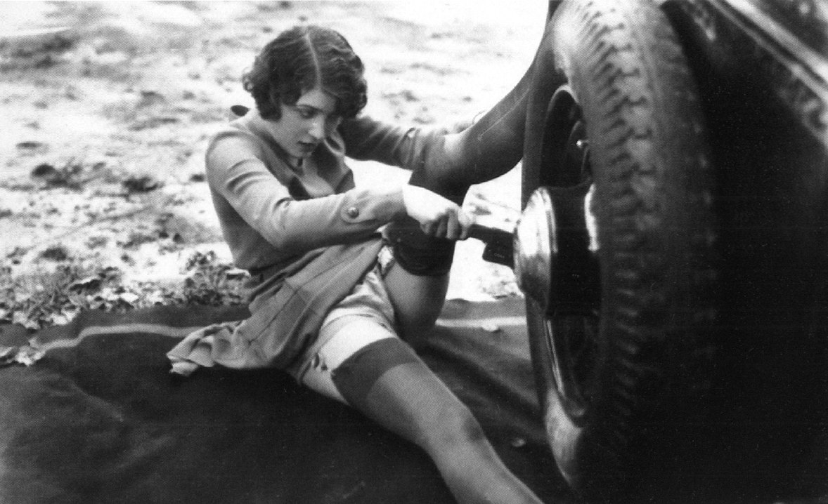 vintage photo risque sexy woman changing tire in stockings