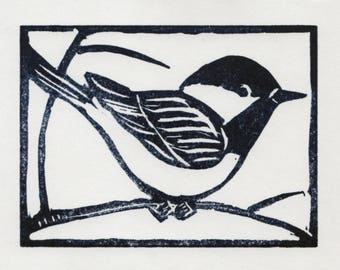 An original linocut print of a black-capped chickadee