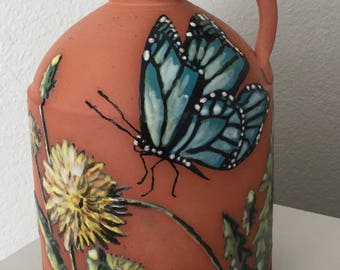 Blue Butterfly hovering over the Dandelions Jug