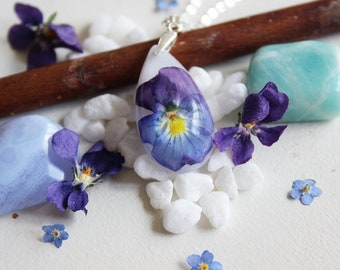White resin inlaid with a blue and purple pansy flower Teardrop Pendant