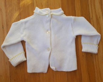 Friedknit all-cotton white sweater with stylish lemon-meringue-colored striping and a button-up front for the dashing 9-to-12-month old