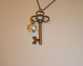 antique brass skeleton key with pearl charm