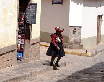Peruvian woman crossing a small street in Cuzco, Peru.