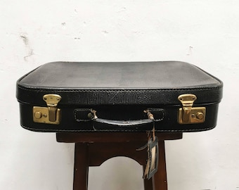 Black vintage suitcase with Golden closures and label