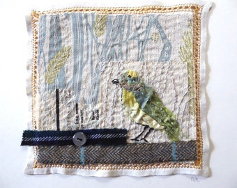 Textile picture of an embroidered greenfinch bird in a stitched grass wheat field