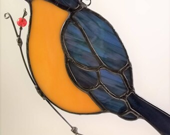 Stained glass blue bird, dark streaky glass with yellow breast, sits on a wire with berries