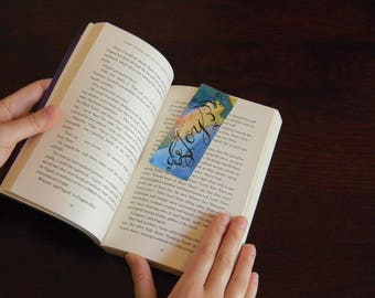 """Rainbow watercolor bookmark with """"Joy"""" word written with black marker"""
