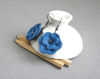 Boucles d'oreilles fleurs bleu jean posées sur une estampe en métal, boucles d'oreilles baroques romantiques, fleur bleu en relief pâte fimo