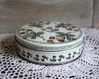 Floral/roses/butterflies/white/red/green/circle/tin. Cute tin. Adorable butterflies, bumble bees, and floral print. Pretty!